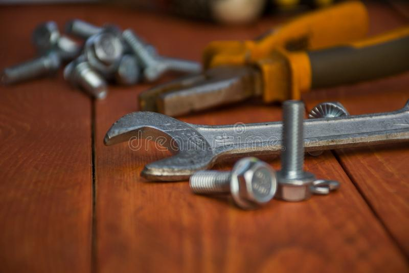 Key emphasis . Closeup of a wrench with bolts on a wooden table. Medium size wrench with metal bolts, close, in the background, flat-nose pliers. key emphasis stock photography