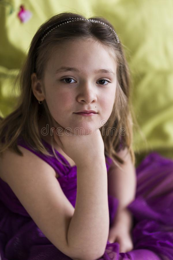Little girl in purple party dress sitting on pale green embroidered bedspread royalty free stock images