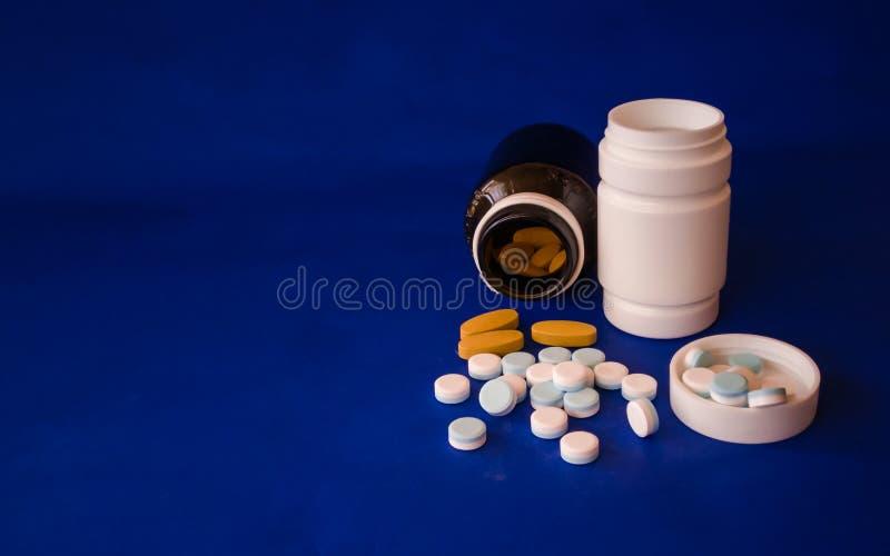 Medizin und Medizinflaschen auf einem blauen Hintergrund lizenzfreie stockfotos