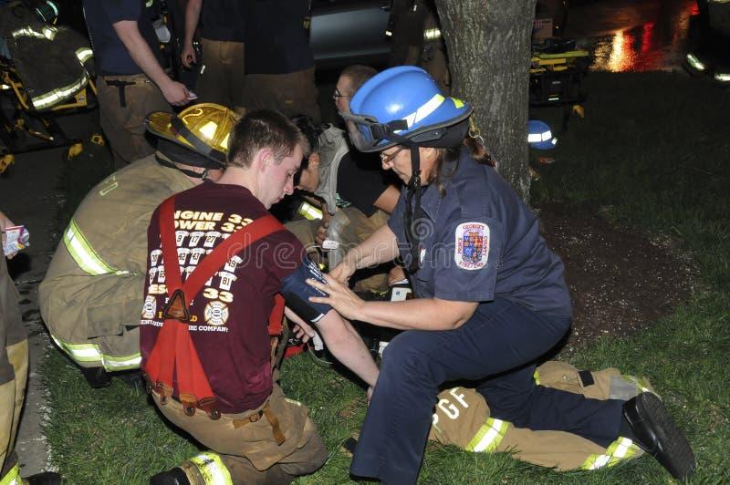 Mediziner, die Blutdruck des Feuerwehrmanns nehmen stockfotos