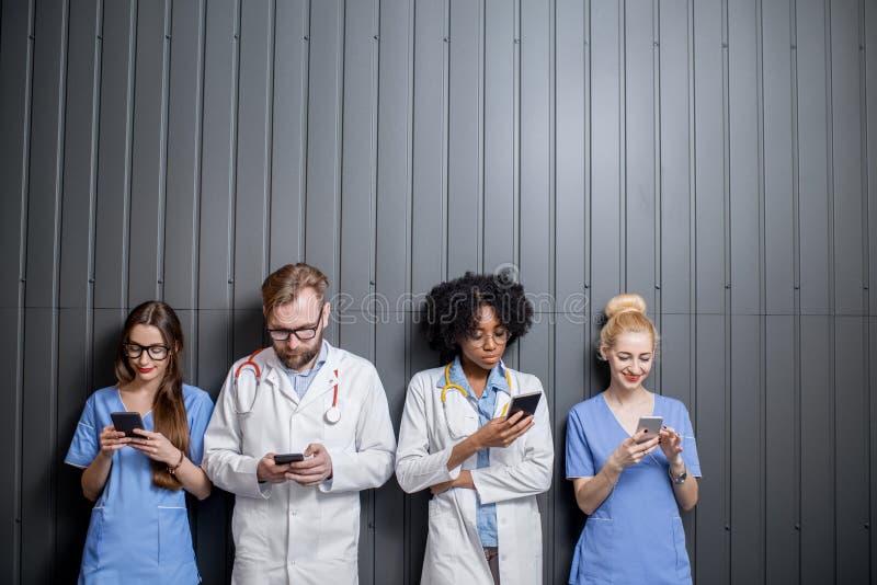 Mediziner mit Telefonen zuhause lizenzfreie stockfotos