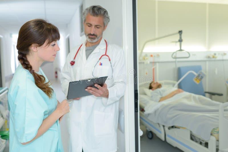 Medizinische Arbeitskräfte, die Klemmbrett außerhalb geduldigen ` s Raumes betrachten lizenzfreies stockbild