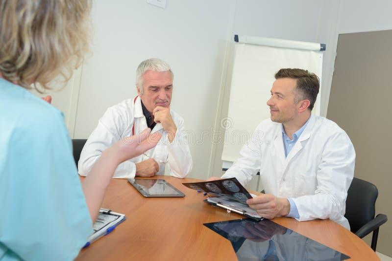 Medizinische Arbeitskräfte, die Röntgenstrahlergebnisse dicussing sind lizenzfreie stockbilder