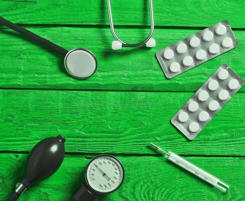 Medizinische Bedarfe auf farbigem Holztisch Stethoskop, Tablette, Thermometer stockfotos
