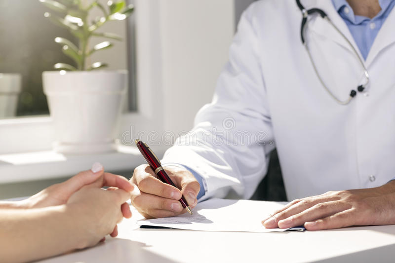 Medizinische Beratung - Doktor und Patient, die durch die Tabelle sitzen lizenzfreies stockbild