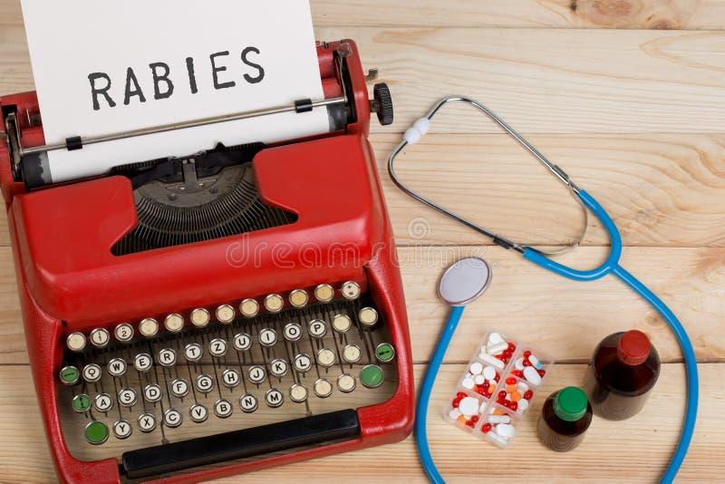 medizinische Diagnose - Doktorarbeitsplatz mit blauem Stethoskop, Pillen, rote Schreibmaschine mit Text Tollwut lizenzfreie stockfotografie