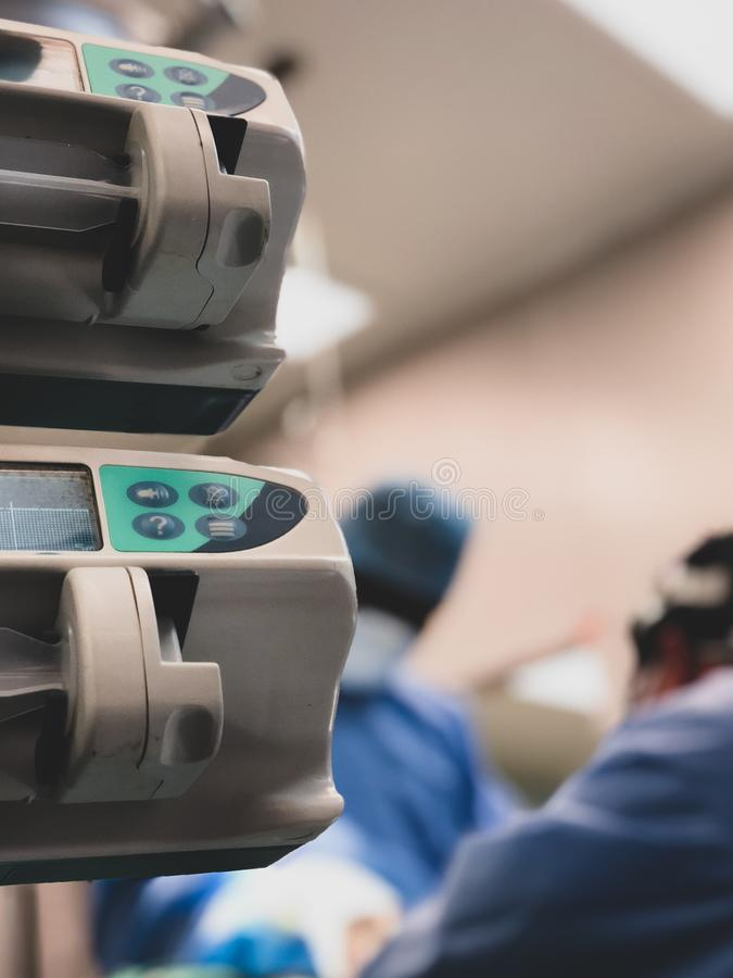 Medizinische Drogeninfusionspumpen im Vordergrund mit 2 Chirurgen, die im selektiven Fokus des Hintergrundes - Szene vom operatin lizenzfreie stockfotografie