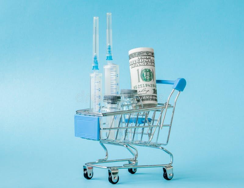 Medizinische Einspritzung und Dollar in Einkaufslaufkatze auf blauem Hintergrund Kreative Idee f?r Gesundheitswesenkosten, Drugst lizenzfreies stockfoto