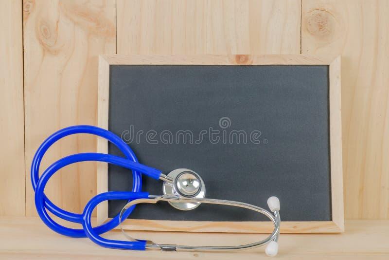 Medizinische Konzept-Tafel mit Stethoskop auf hölzernem Hintergrund lizenzfreie stockfotos