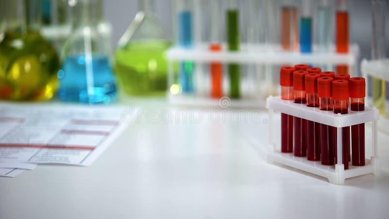 Medizinische Laborant-Holdingkapsel, Blutproben auf Hintergrund, pharmazeutische Produkte lizenzfreies stockbild