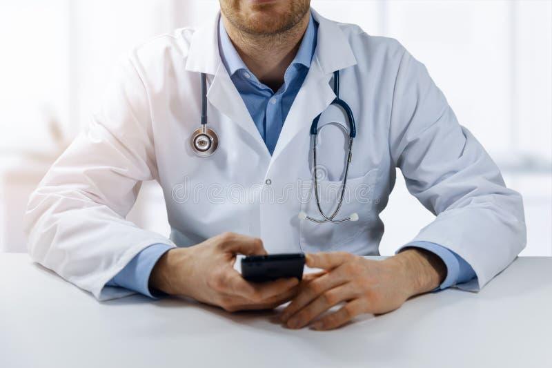 Medizinische on-line-Beratung - Arzt, der durch die Tabelle sitzt und intelligentes Telefon verwendet stockfoto