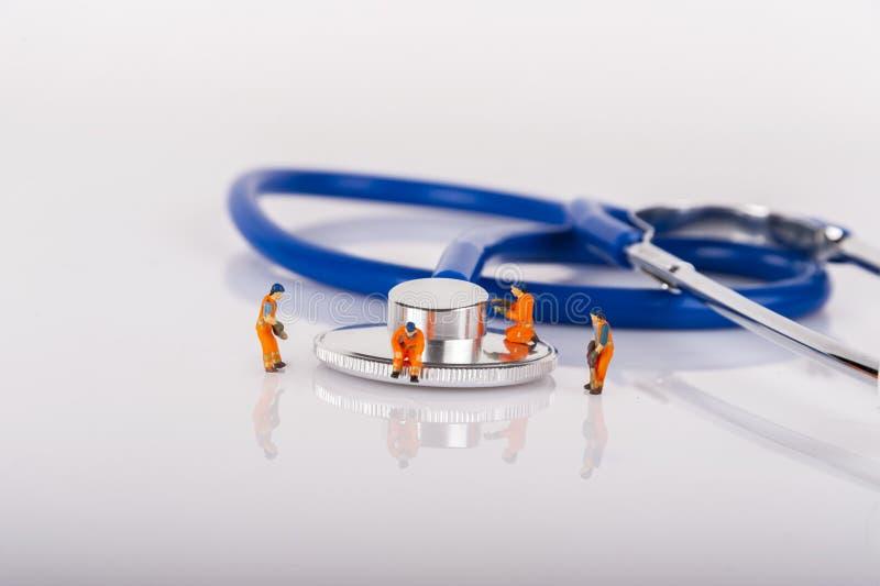 Medizinische Miniaturleute, Arbeitskräfte auf medizinischer Ausrüstung stockfotos