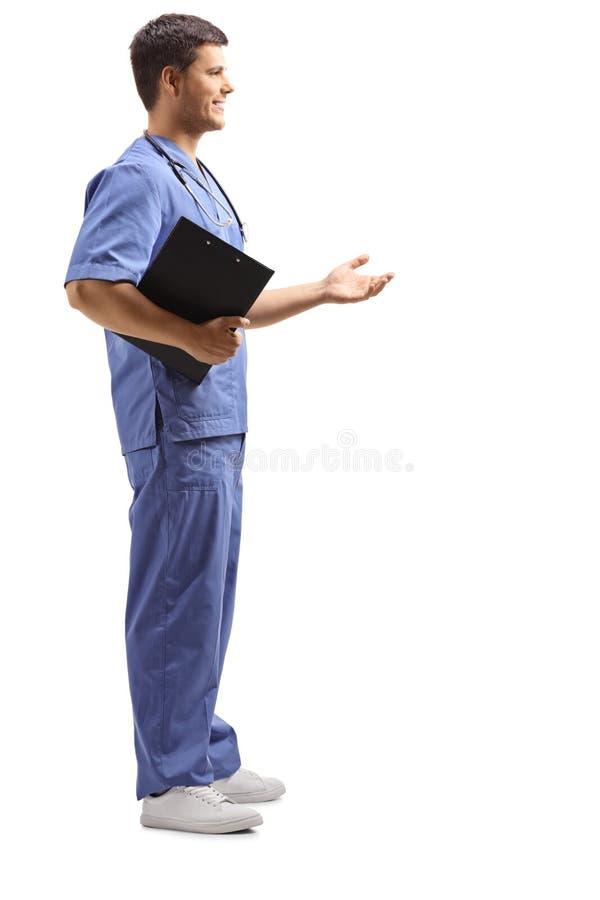 Medizinische Person in einer blauen Uniform, die ein Klemmbrett hält und mit der Hand gestikuliert lizenzfreie stockfotografie