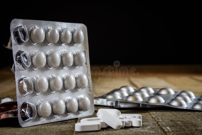 Medizinische Tabletten auf einem Holztisch Weiße Pillen im Plastik-contai lizenzfreie stockfotos