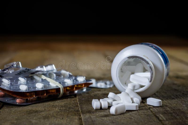 Medizinische Tabletten auf einem Holztisch Weiße Pillen im Plastik-contai lizenzfreies stockfoto