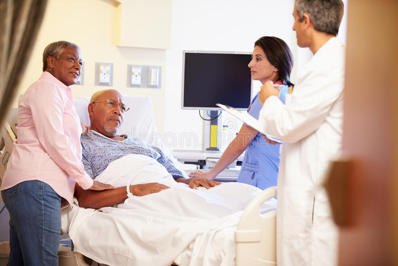 Medizinischer Team Meeting With Senior Couple im Krankenhauszimmer lizenzfreie stockbilder