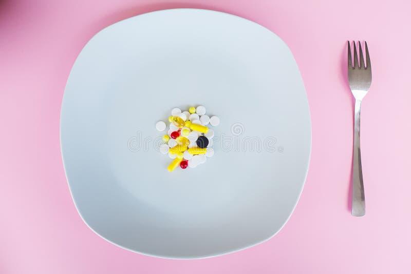 MEDIZINISCHES Konzept Farbige Pillen und Kapsel auf Platte mit Gabel P lizenzfreie stockfotografie