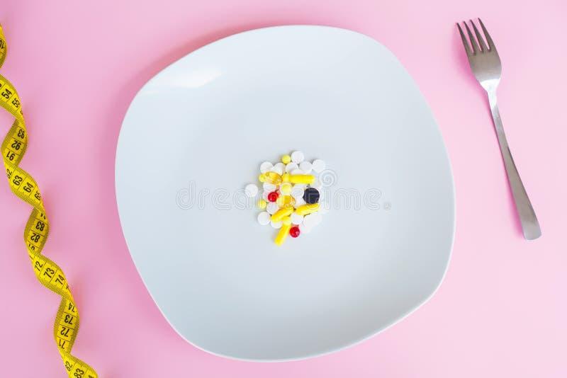 MEDIZINISCHES Konzept Farbige Pillen und Kapsel auf Platte mit Gabel P stockfotografie