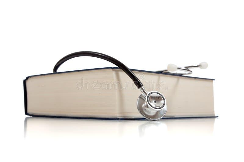 Medizinisches Nachschlagbuch mit einem Stethoskop auf Weiß lizenzfreies stockbild