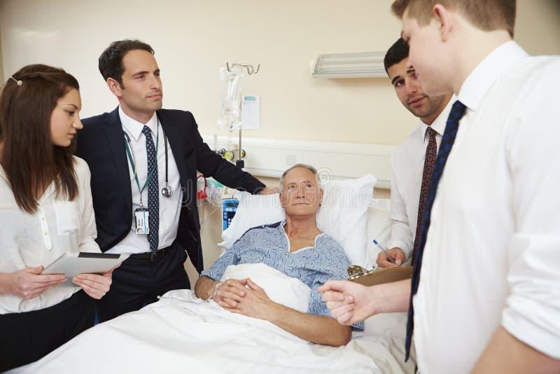 Medizinisches Personal auf den Runden, die das Bett des männlichen Patienten bereitstehen lizenzfreies stockfoto
