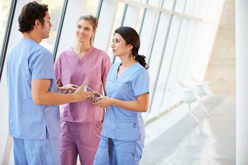 Medizinisches Personal, das im Krankenhaus-Korridor mit Digital-Tablette spricht lizenzfreies stockfoto