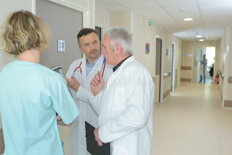 Medizinisches Personal, das im Krankenhauskorridor konferiert stockfotografie