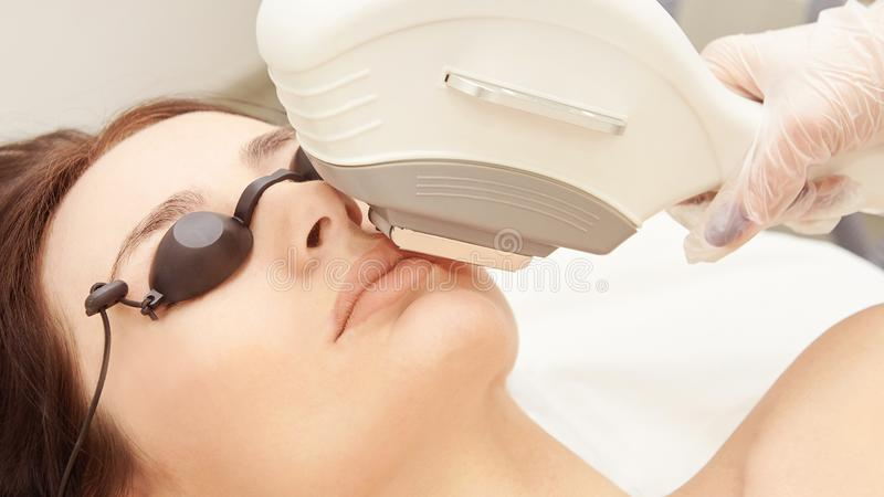 Medizinisches Schönheitslaser-cosmeology Verfahren Junge Frau am Salon Berufsdoktor Frau skincare Technologie Haarabbau lizenzfreie stockfotos
