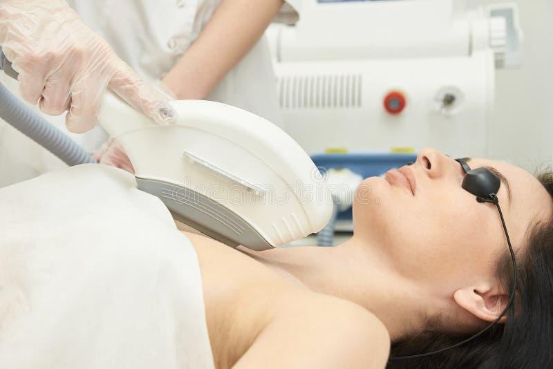 Medizinisches Schönheitslaser-cosmeology Verfahren Junge Frau am Salon Berufsdoktor Frau skincare Technologie Haarabbau lizenzfreie stockfotografie