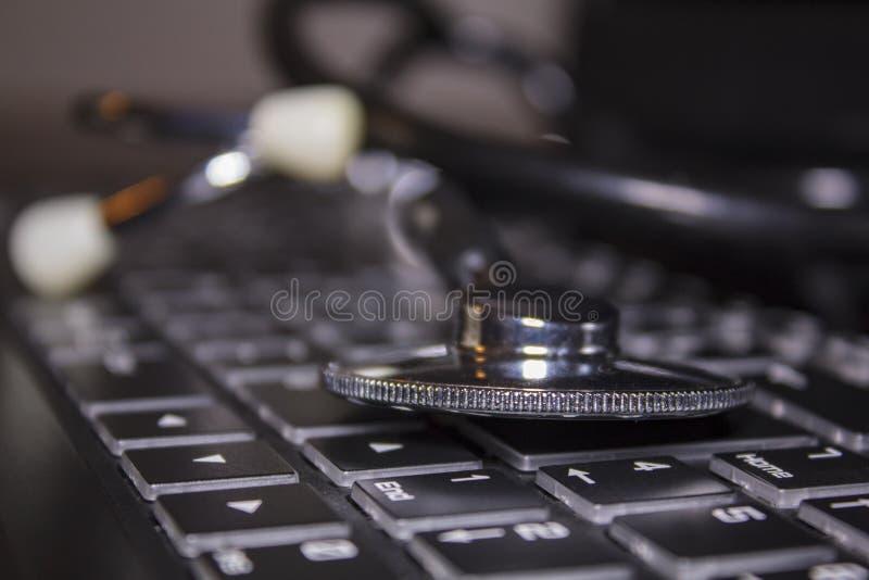 Medizinisches Stethoskop auf Laptoptastatur lizenzfreies stockbild