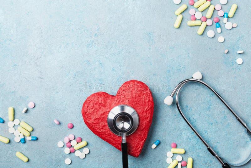 Medizinisches Stethoskop, rotes Herz und Drogenpillen auf Draufsicht des blauen Hintergrundes Konzept des gesunden und Blutdrucke stockfoto