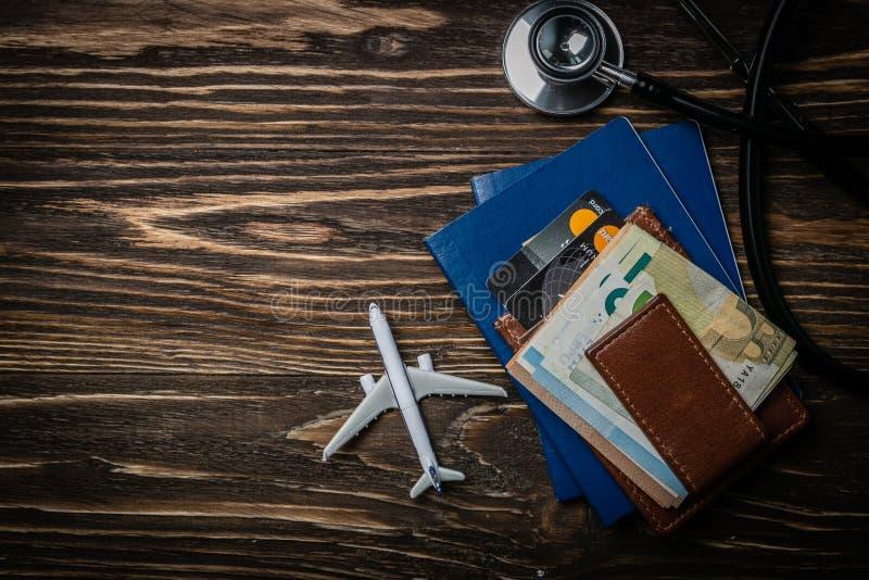 Medizinisches Tourismuskonzept - Pässe, Stethoskop, Flugzeug, Geld lizenzfreie stockfotos