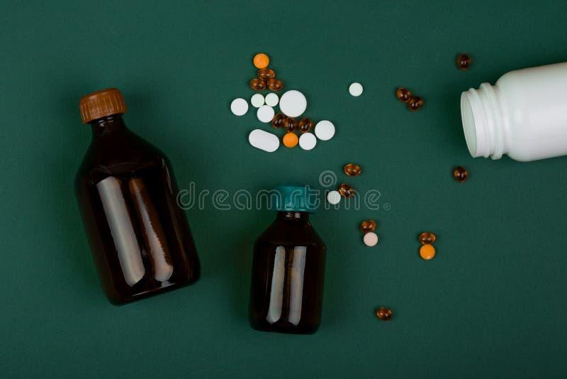 Medizinkonzept - Pillen und medizinische Flaschen auf Grünbuchhintergrund stockfotos
