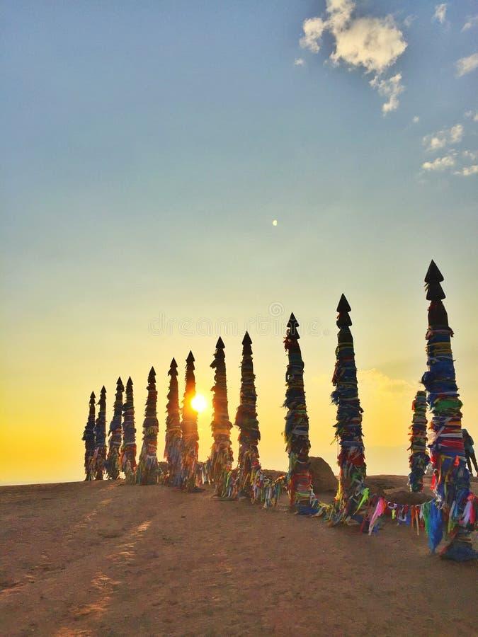 Medizinmannsäule Hölzerne Medizinmanntotems unter Sonnenuntergang bei Burhan Cape, Baikal See lizenzfreies stockbild