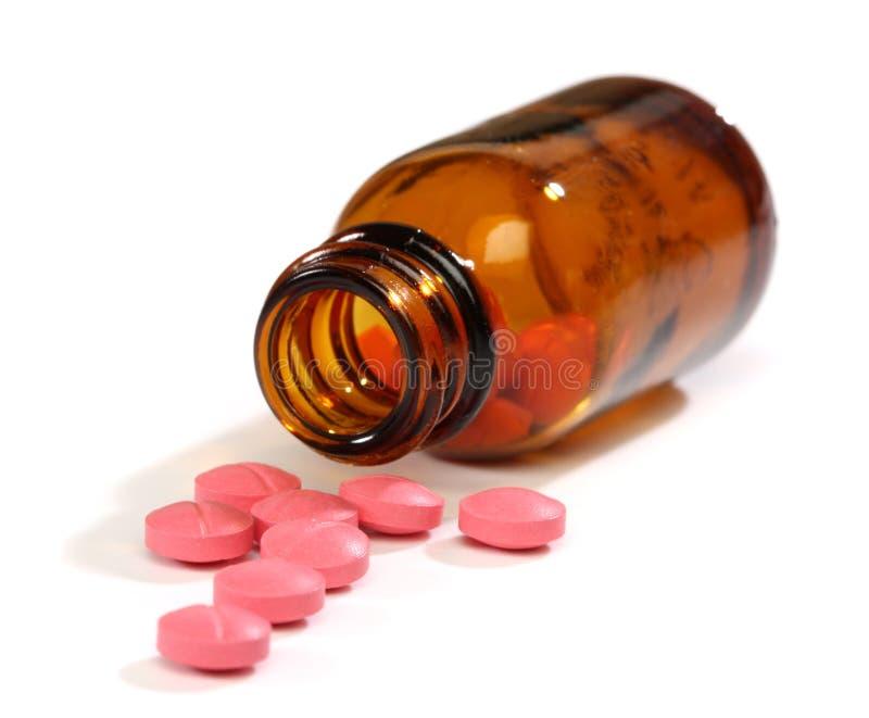 Medizinpillen, die eine Flasche überlaufen stockfotografie