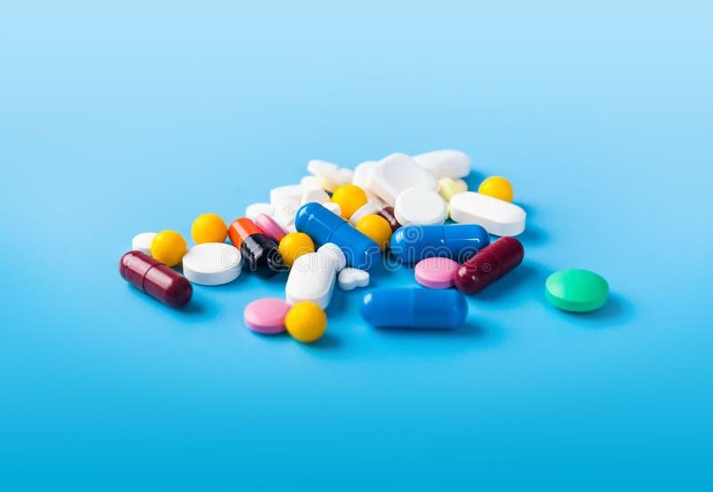 Medizinpillen, -tabletten und -kapseln über blauem Hintergrund lizenzfreie stockfotos