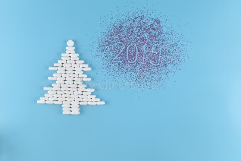 Medizinpillenform des Weihnachtsbaums auf blauem Hintergrund Konzeptweihnachten und neues Jahr 2019 stockbilder
