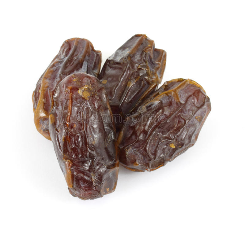 Medjool dates. Several large medjool soft dates on a white background royalty free stock photos
