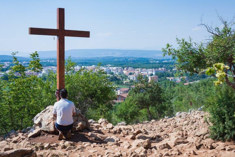 Medjugorje, Bośnia, Herzegovina i Lipiec, - 6 2012: Modlenie przed drewnianym krzyżem w sławnej pielgrzymce i zdjęcia royalty free