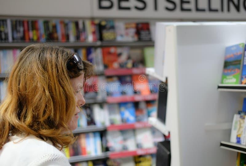 Medlem av där som ses offentligt se böcker som sett i en storgatannewsagent och bokhandel fotografering för bildbyråer