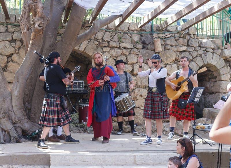 Medlem av den årliga festivalen av riddare av Jerusalem som är iklädda en skotsk nationell klänning som utför på musikplatsen arkivbild