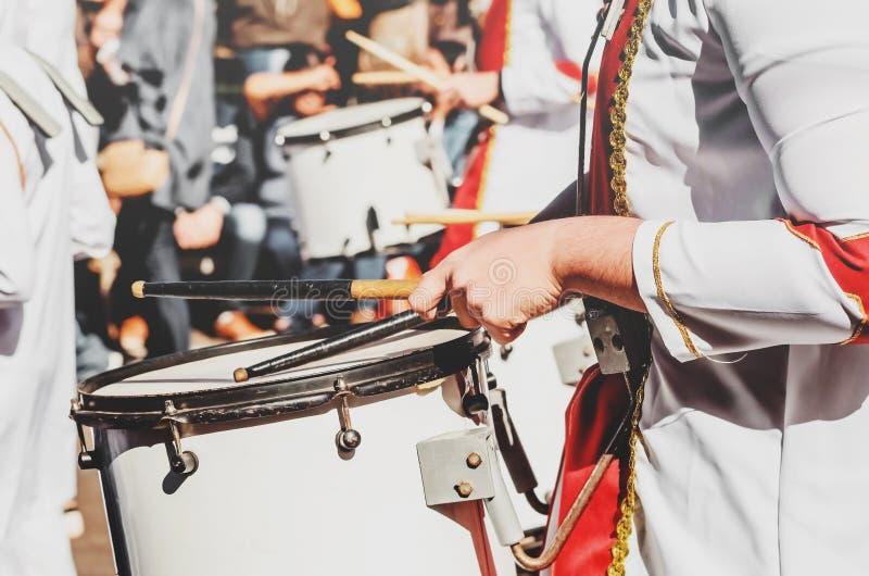 Medlem av en militär fanfar som spelar en mobil bastrumma på en medeltal fotografering för bildbyråer