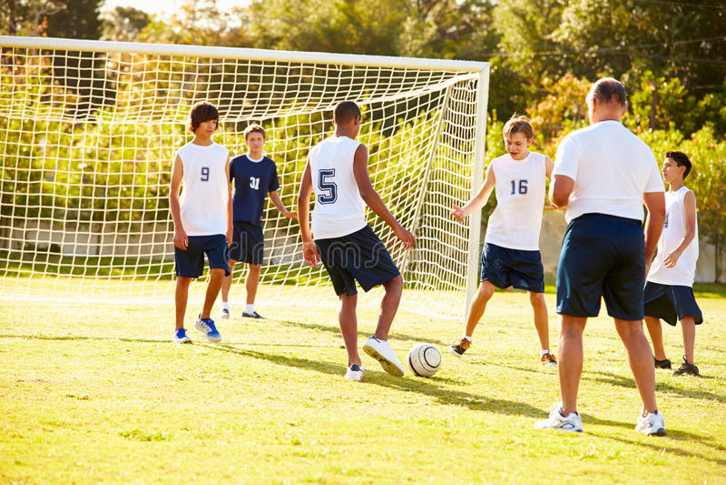 Medlemmar av manlig högstadiumfotboll som spelar matchen royaltyfri foto