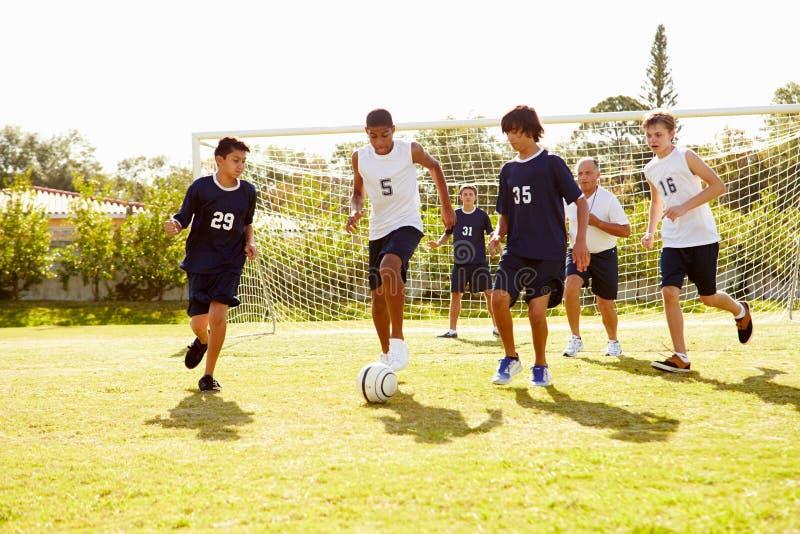 Medlemmar av manlig högstadiumfotboll som spelar matchen royaltyfri bild