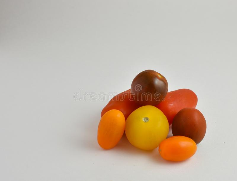 Medley of heirloom tomatoes on white background with copy space. Diverse medley of heirloom tomatoes on white background with copy space royalty free stock image