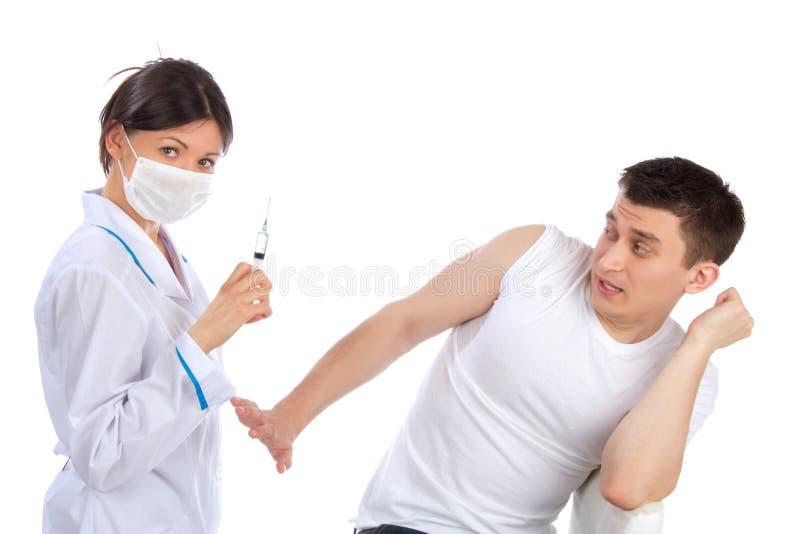 Medo do doutor e do homem da fobia das injeções da seringa fotografia de stock