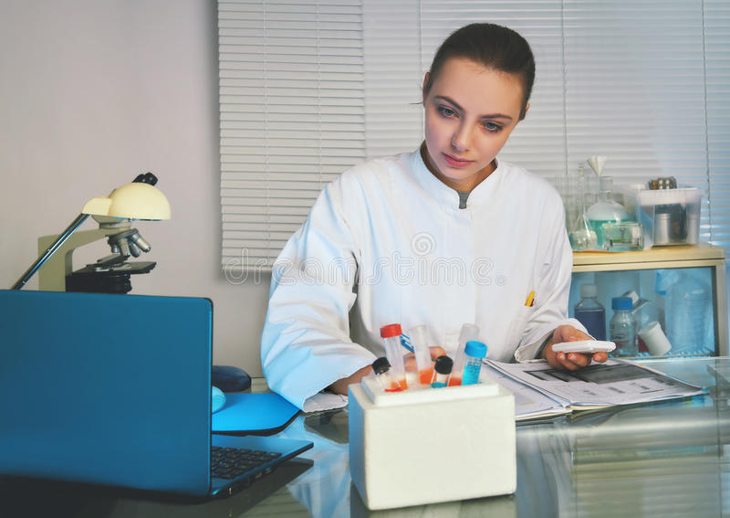 Medtech no revestimento branco que trabalha com amostras dos pacientes imagens de stock