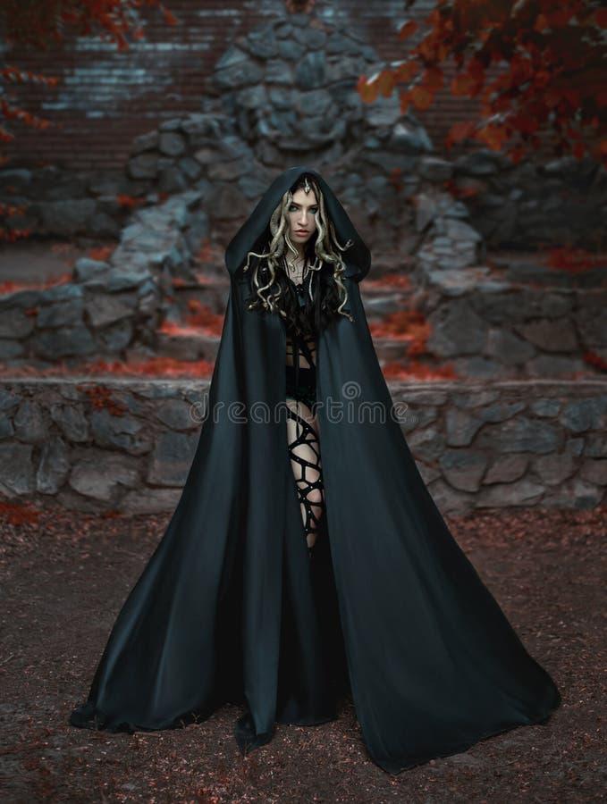 MedusaGorgona gudinna som vänder en blick in i en sten Det står på bakgrunden av en stenbiskopsstol med röda bloodstains royaltyfri bild