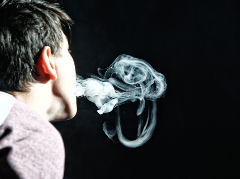 Medusas del truco de Vape en el funcionamiento del vaper en fondo oscuro fotografía de archivo