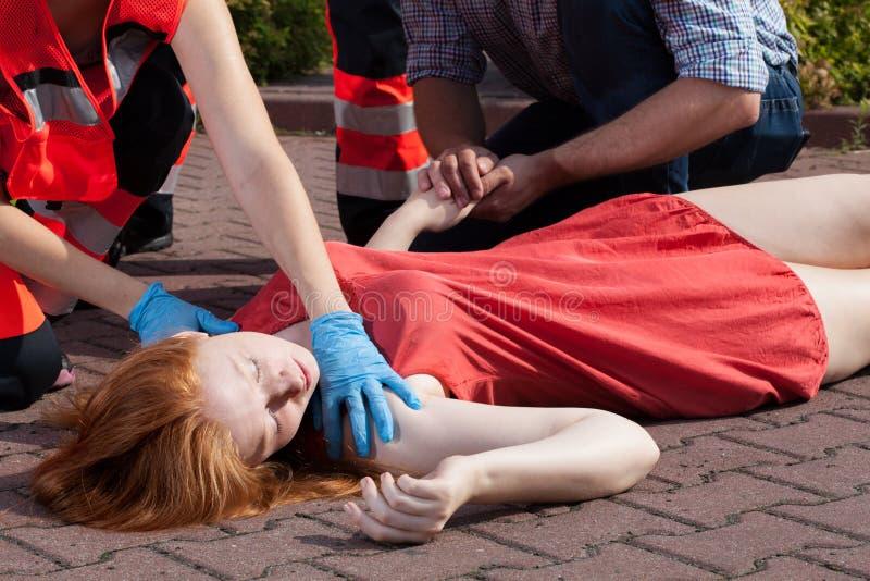 Medvetslös kvinna för paramedicinsk portion arkivfoton