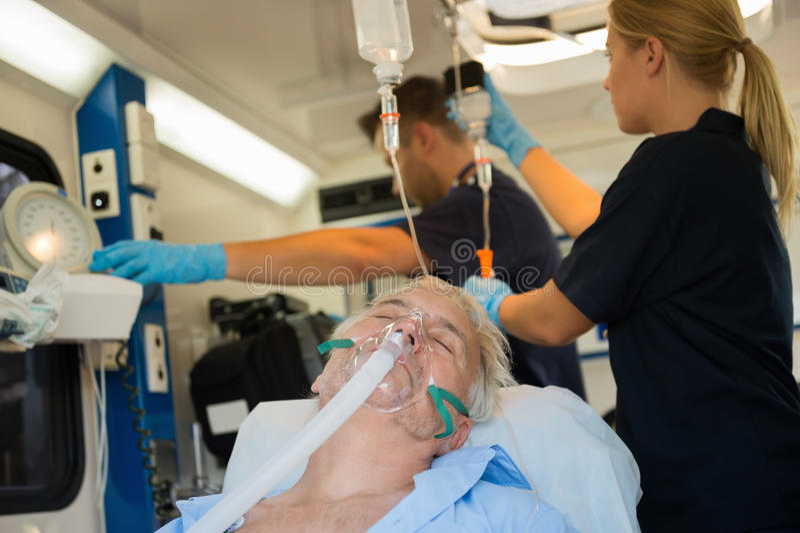 Medvetslös patient med syremaskeringen i ambulans arkivfoto